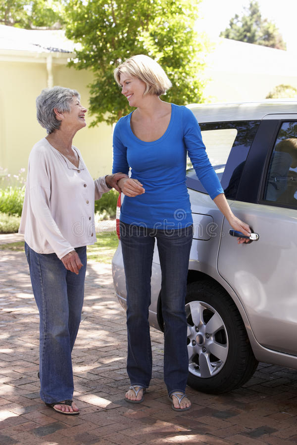 Hög kvinna för kvinnaportion in i bilen arkivbild