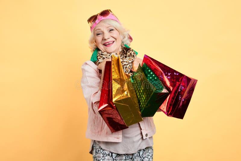 Hög kvinna för lycklig gladlynt glamour med shoppingpåsar som isoleras på guling arkivbilder