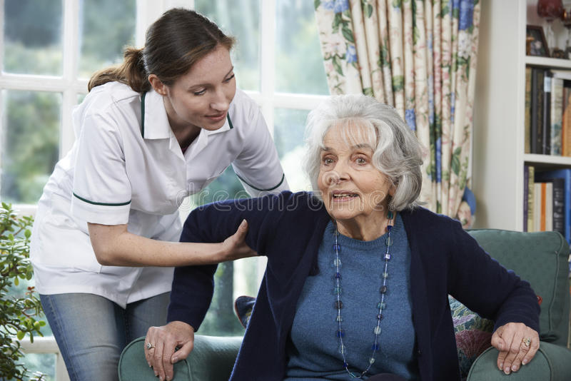 Hög kvinna för omsorgarbetarportion som ska fås upp ut ur stol fotografering för bildbyråer