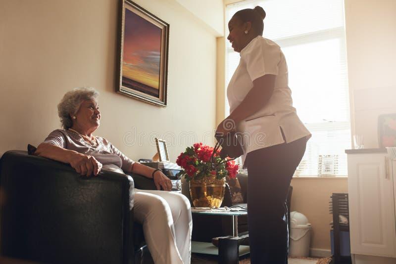 Hög kvinna hemma med den kvinnliga anhörigvårdaren royaltyfri bild