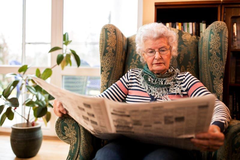 Hög kvinna, i att koppla av för pansion som är hemmastatt, medan läsa en newspap arkivfoton