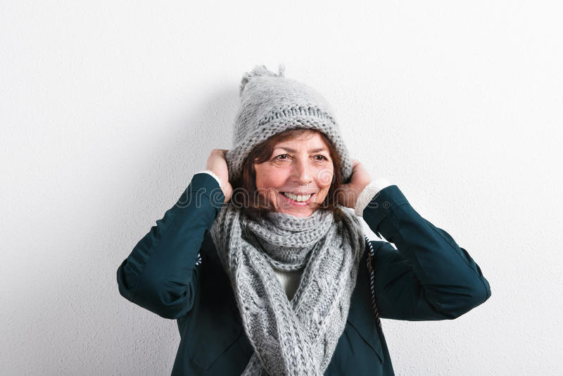 Hög kvinna i den woolen halsduken och hatten, studioskott fotografering för bildbyråer