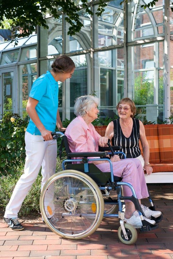 Hög kvinna i en rullstol med hennes vårdare royaltyfria foton