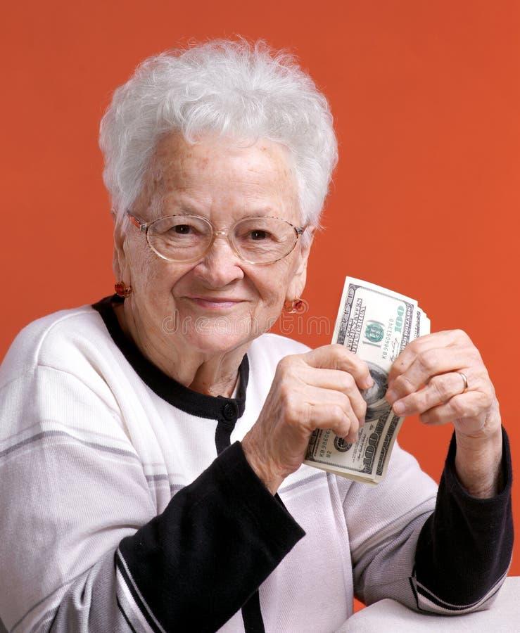 Hög kvinna i exponeringsglasinnehavpengar royaltyfria foton