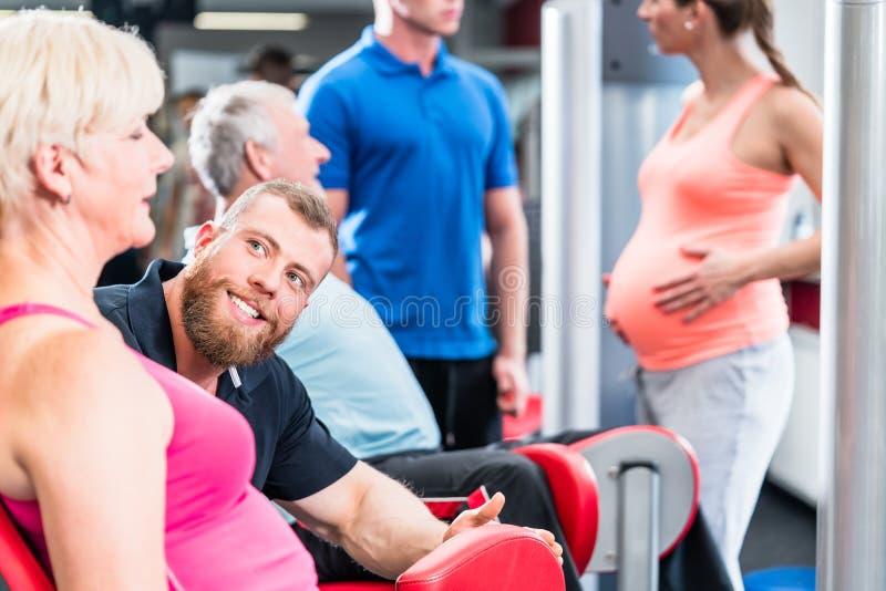 Hög kvinna i grupp med gravida kvinnan som utarbetar på idrottshallen royaltyfria bilder