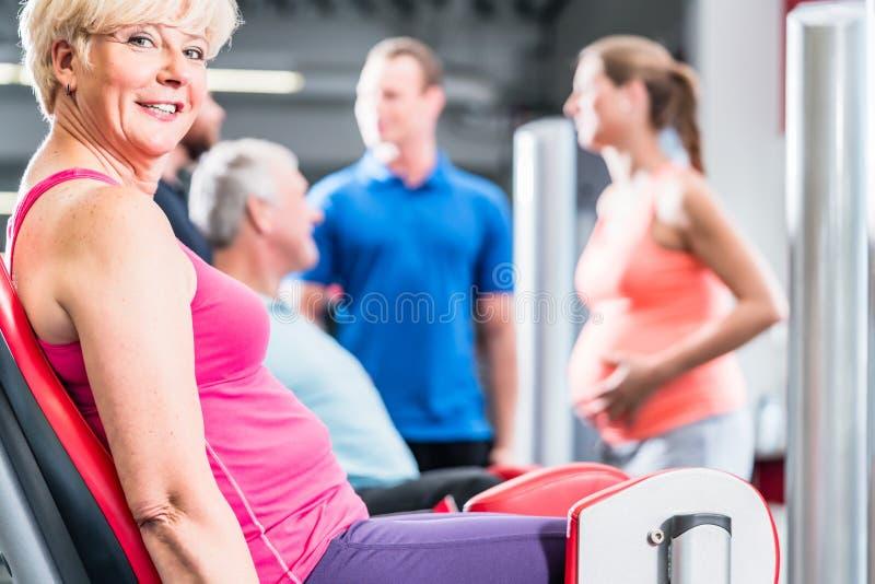 Hög kvinna i grupp med gravida kvinnan som utarbetar på idrottshallen royaltyfri foto