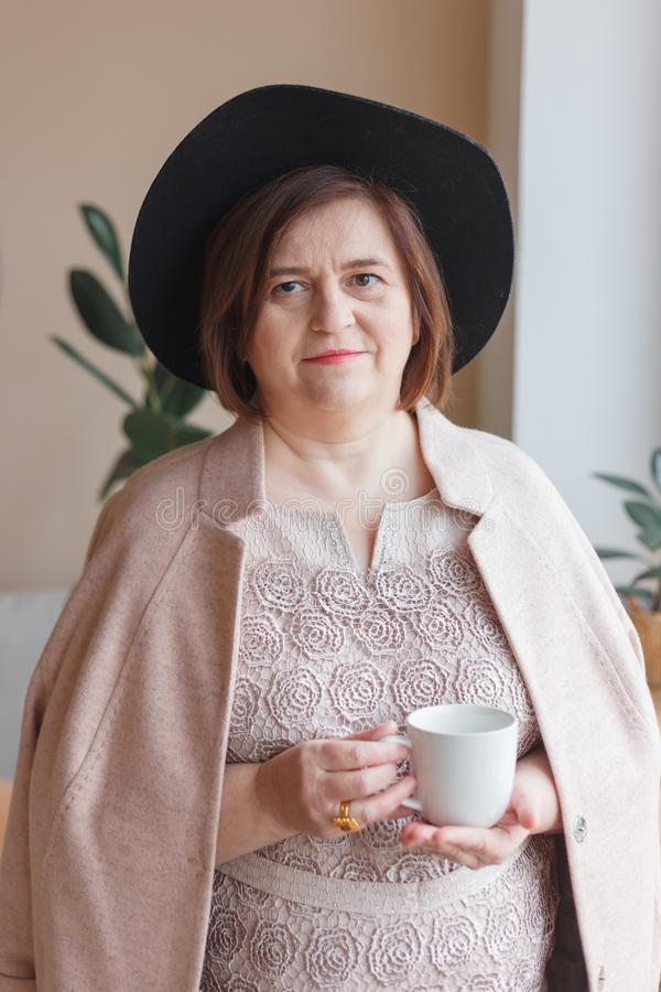 Hög kvinna i hatt nära fönster i den moderna lägenhetinre som dricker kaffe royaltyfri foto