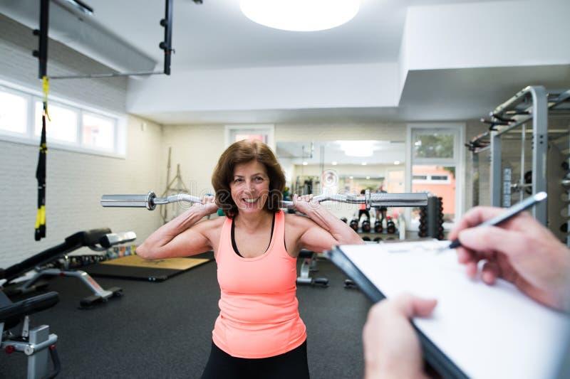 Hög kvinna i idrottshall som utarbetar med vikter royaltyfria foton
