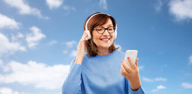 Hög kvinna i lyssnande musik för hörlurar på cellen arkivfoton
