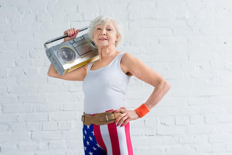 hög kvinna, i patriotisk bandspelare och att le för sportswearinnehav royaltyfria foton