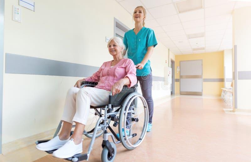Hög kvinna i rullstol med sjuksköterskan i sjukhus arkivbild