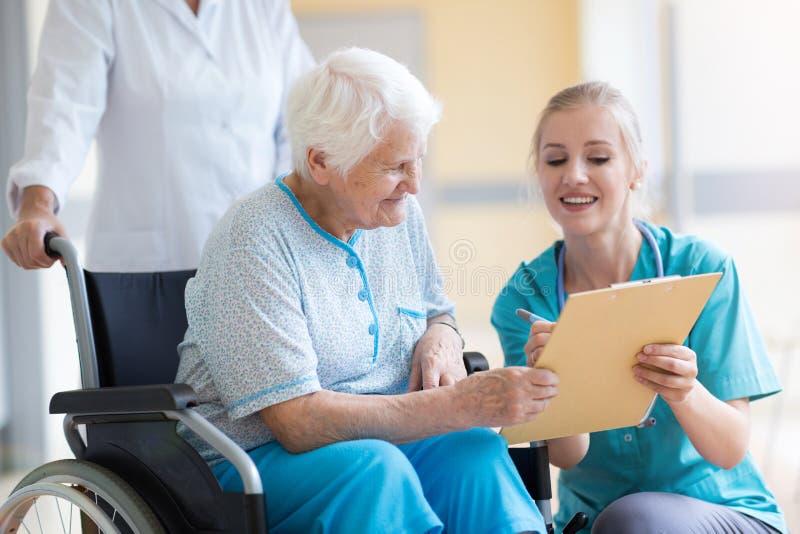 Hög kvinna i rullstol med sjuksköterskan i sjukhus royaltyfri bild
