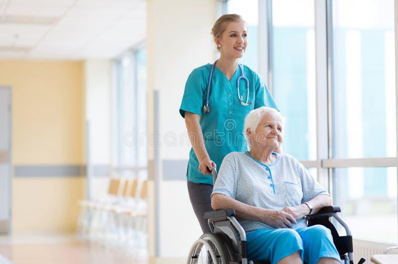 Hög kvinna i rullstol med sjuksköterskan i sjukhus arkivfoto