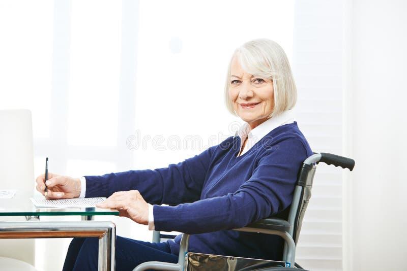 Hög kvinna i rullstol på en tabell arkivfoto