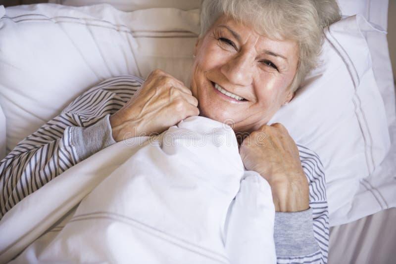 Hög kvinna i säng royaltyfri fotografi