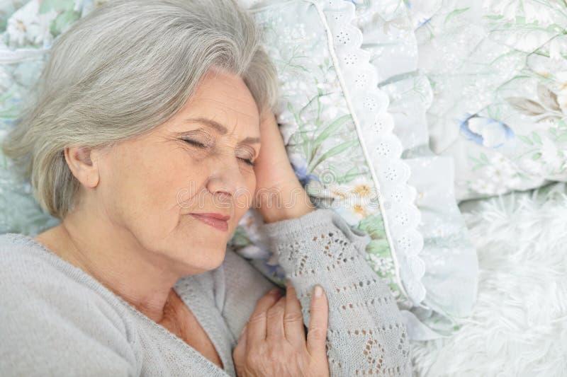 Hög kvinna i säng arkivfoton