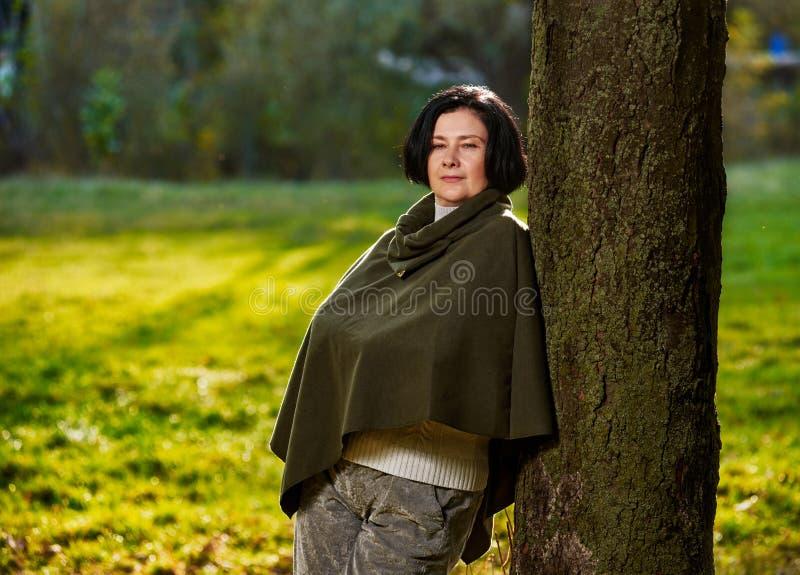 Hög kvinna i skog arkivbild