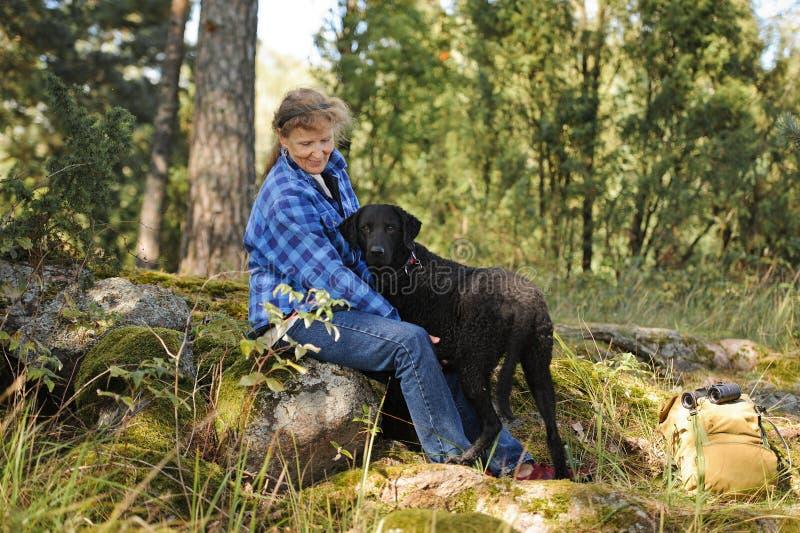 Hög kvinna i skog med den älsklings- hunden arkivfoto