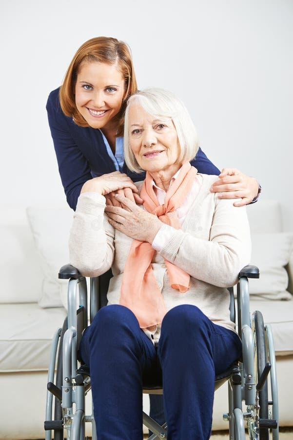 Hög kvinna med anhörigvårdaren från sjukvårdservice royaltyfri fotografi