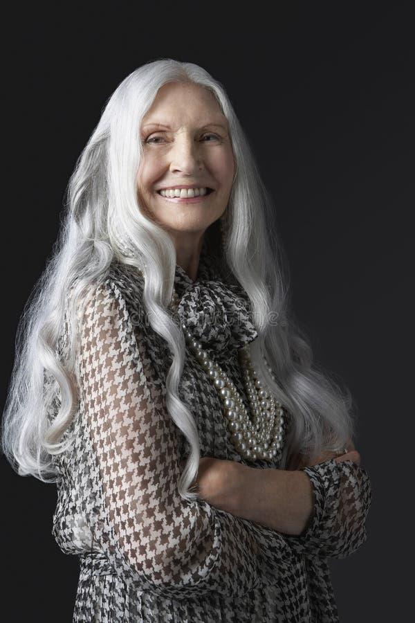 Hög kvinna med armar korsat le royaltyfri fotografi