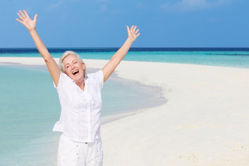 Hög kvinna med armar som är utsträckta på den härliga stranden arkivbild