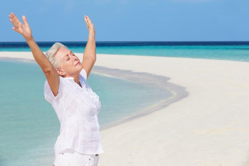Hög kvinna med armar som är utsträckta på den härliga stranden fotografering för bildbyråer