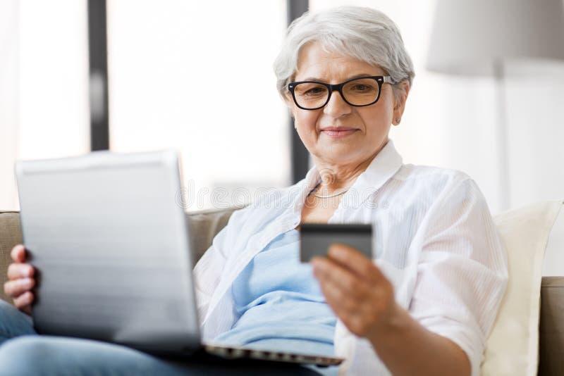 Hög kvinna med bärbara datorn och kreditkorten hemma arkivbilder