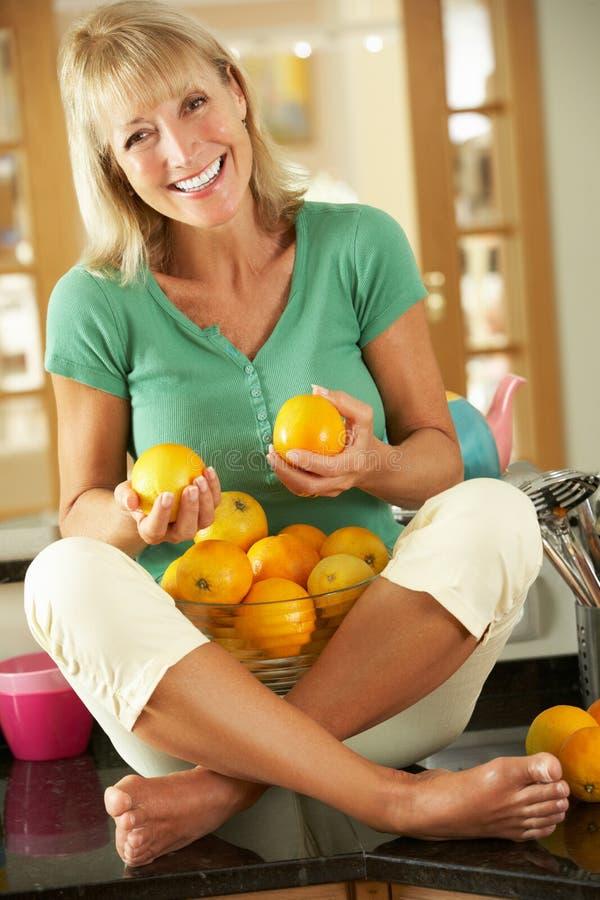 Hög kvinna med bunken av apelsiner arkivbild
