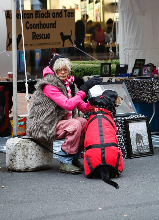 Hög kvinna med coonhounden på adoptionhändelsen arkivbild