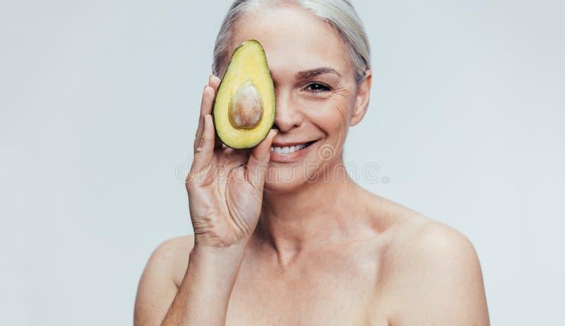 Hög kvinna med en halv avokado arkivbilder