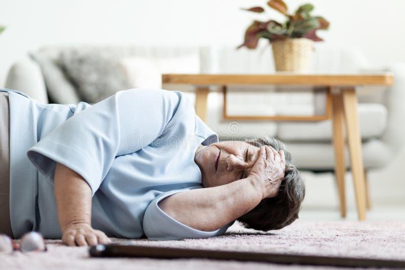 Hög kvinna med en huvudvärk, når att ha fallit ner hemma royaltyfri fotografi