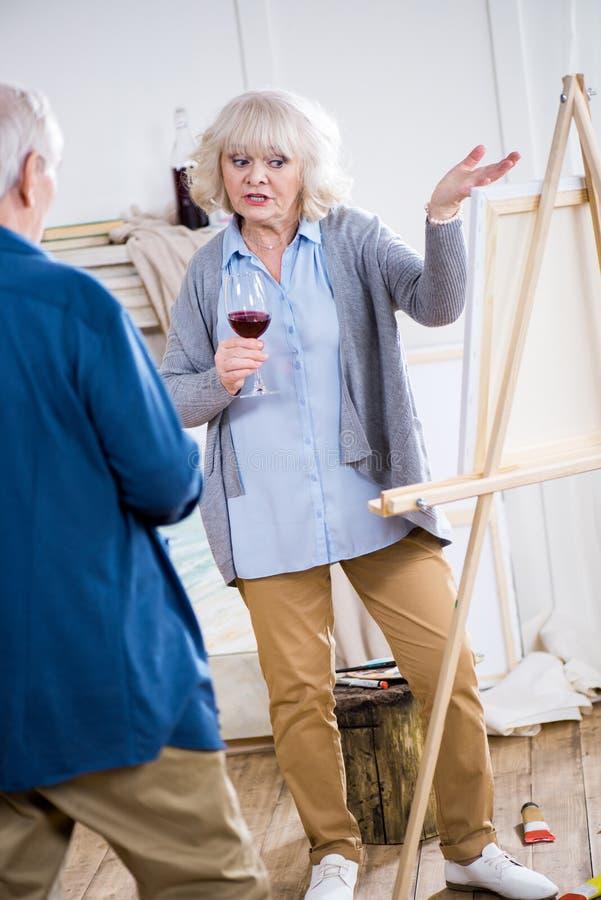 Hög kvinna med exponeringsglas av vin som talar till mannen royaltyfria bilder