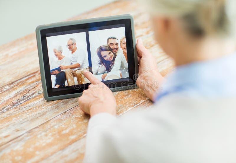 Hög kvinna med familjfotoet på minnestavlaPCskärmen royaltyfri bild