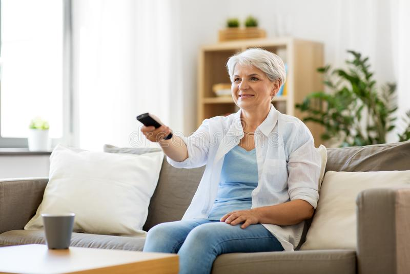 Hög kvinna med hållande ögonen på tv för fjärrkontroll hemma fotografering för bildbyråer
