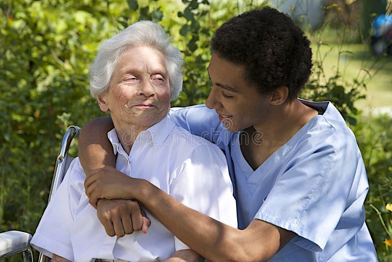 Hög kvinna med henne caregiver royaltyfria bilder