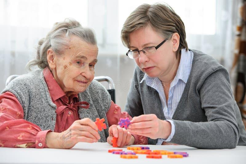 Hög kvinna med hennes äldre omsorgsjuksköterska royaltyfria bilder