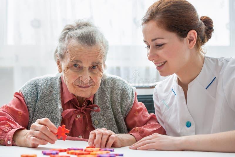 Hög kvinna med hennes äldre omsorgsjuksköterska royaltyfri fotografi