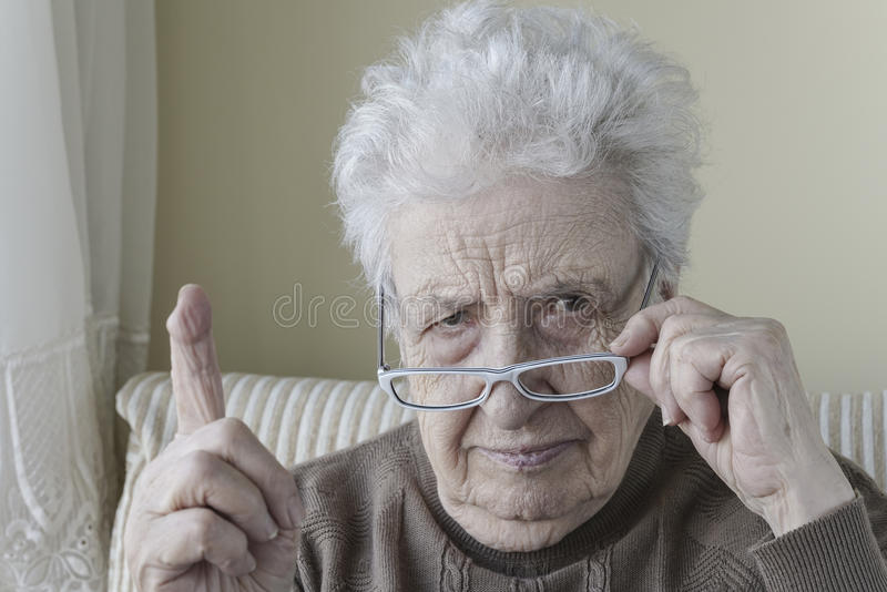 Hög kvinna med hennes finger upp för förmaning/waring royaltyfria bilder