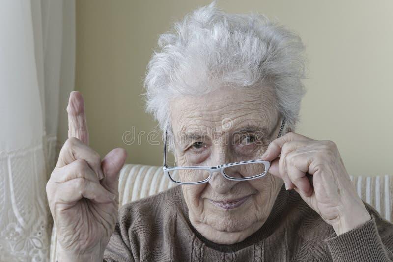 Hög kvinna med hennes finger upp för förmaning/waring royaltyfri fotografi