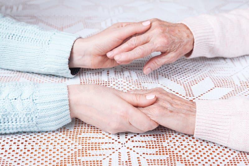 Hög kvinna med hennes hemmastadda anhörigvårdare Rymma händer, closeup för horisontellt bästa sikt royaltyfri fotografi