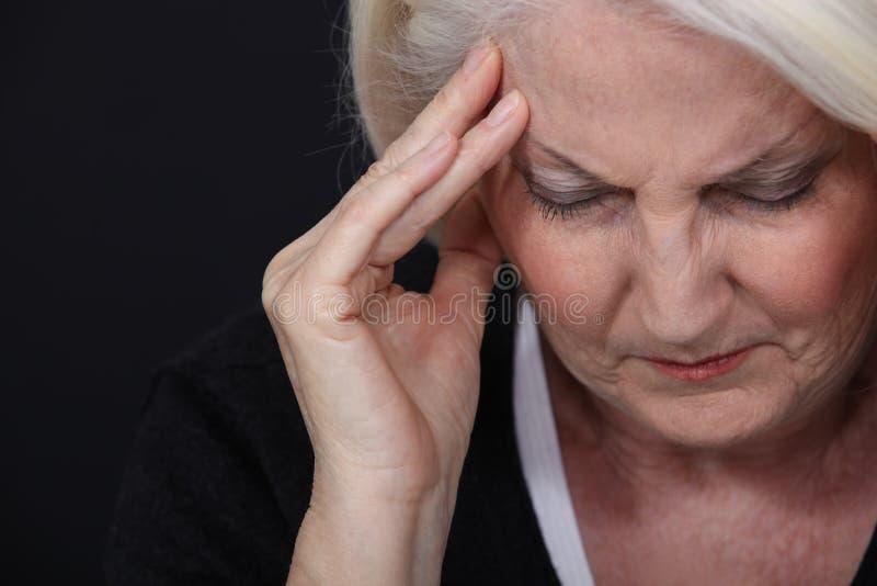 Hög kvinna med huvudvärk arkivfoto
