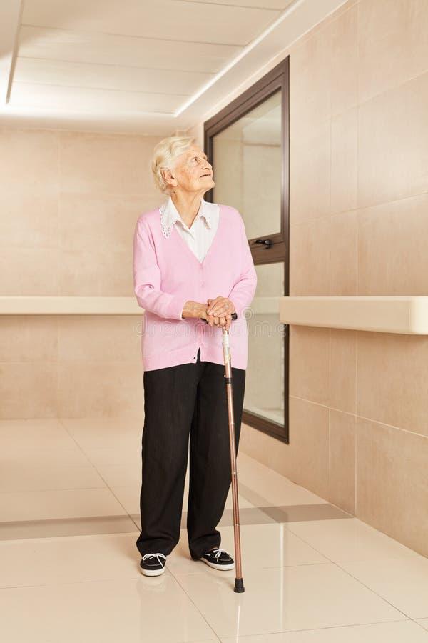 Hög kvinna med kryckan i ett vårdhem arkivfoto