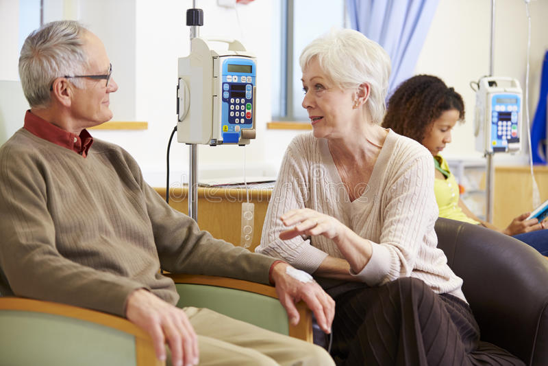 Hög kvinna med maken under kemoterapibehandling royaltyfri foto