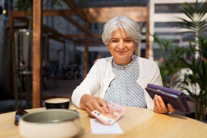 Hög kvinna med pengar som betalar räkningen på kafét royaltyfri foto