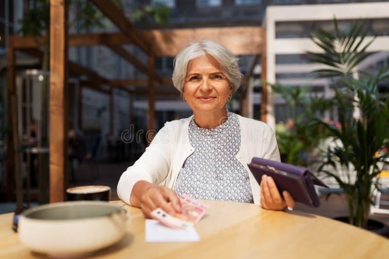 Hög kvinna med pengar som betalar räkningen på kafét arkivbilder