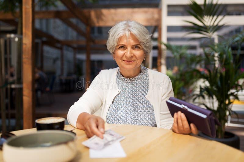 Hög kvinna med pengar som betalar räkningen på kafét arkivfoton