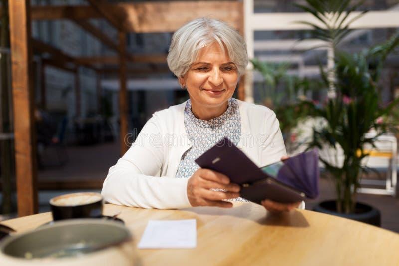 Hög kvinna med plånboken som betalar räkningen på kafét royaltyfri fotografi