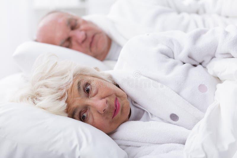 Hög kvinna med sömnlöshet arkivfoto