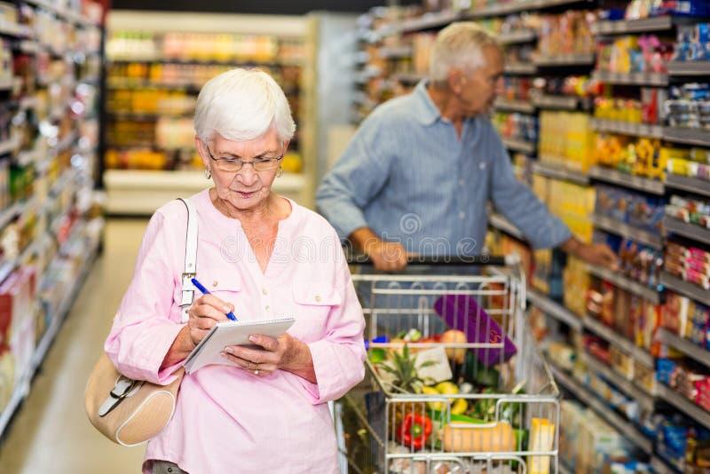 Hög kvinna med shoppinglistan royaltyfri bild