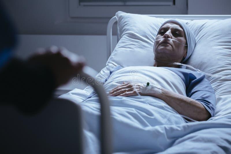 Hög kvinna med sjaletten i sjukhussäng under kemoterapi arkivfoto